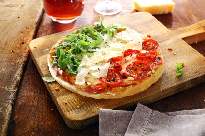 Colourful Italian pizza in the national colours topped with fresh green rocket leaves, white shavings of cheese and red tomatoes in three stripes standing on a wooden board on an old rustic table